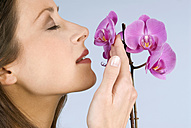 Young woman smelling flowers, close-up - WESTF04817