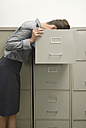 Businesswoman looking through filing cabinet - WESTF04762