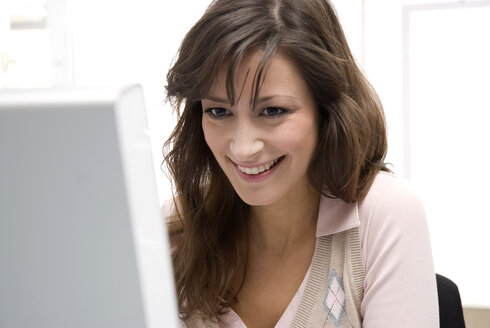 Young woman working in office, smiling, close-up - WESTF04721