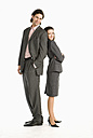 Businessman and businesswoman standing back to back, smiling - WESTF04694