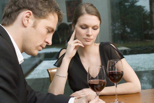 Couple drinking red wine looking unhappy - NHF00534
