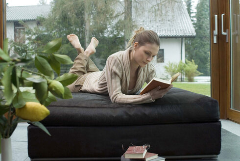Young woman relaxing on sofa reading a book - NHF00435
