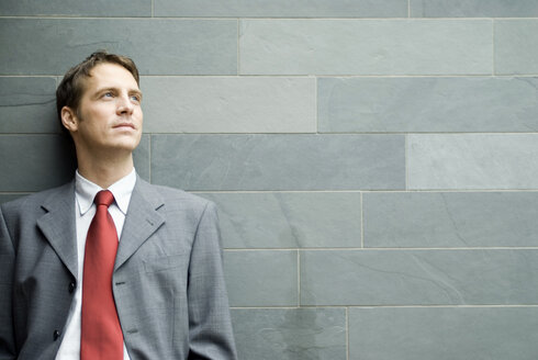Businessman leaning against wall - NHF00414