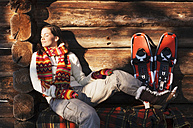 Woman with snowshoes sitting in front of hut - HHF01361
