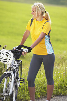 Female cyclist standing next to bike - MRF00890