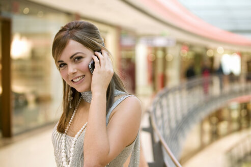 Young woman using mobile phone, portrait - KMF01007