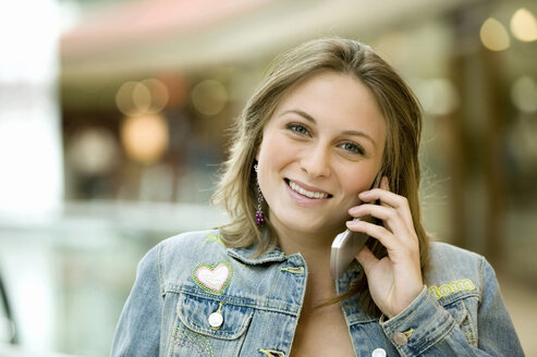 Young woman using mobile phone, portrait - KMF00995