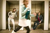 Two women leaning on lift door one woman running - KMF00985