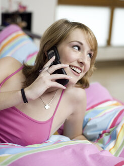 Young woman lying in bed, using mobile phone - KMF00981