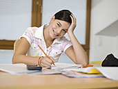 Young woman sitting on desk, writing - KMF00975