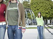 Young woman leaning on pole, watching couple - KMF00972