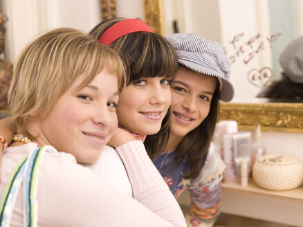 Three girl friends looking to camera, smiling, portrait - KMF00936