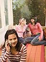 Girl (16-17) phoning, girl friends sitting in backgroud - KMF00933
