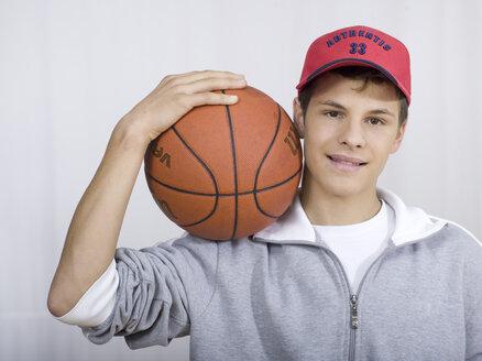 Boy ( 16-17) holding basket ball, portrait - KMF00885