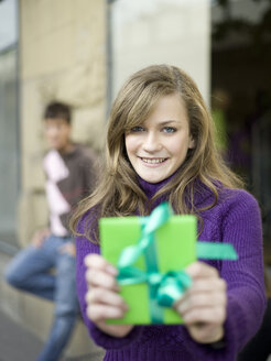 Young woman holding gift, man leaning in background - KMF00879