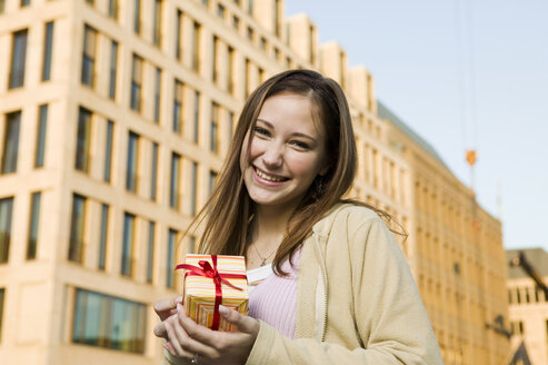 Young woman, holding gift - KMF00825
