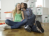 Couple sitting on floor, man kissing woman - WESTF05161