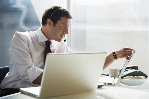 Business man sitting at desk, using head set - WESTF05467