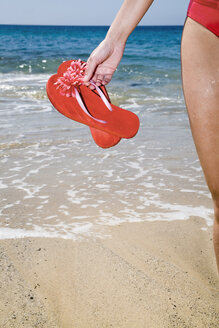 Woman holding flip-flops, close-up - LDF00490