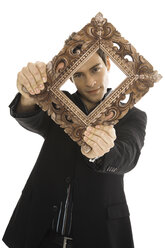 Young man holding picture frame, close-up - PKF00172
