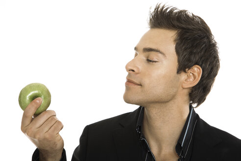 Young man holding green apple, close-up - PKF00151