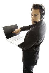Young man wearing head set, holding laptop, close-up - PKF00139