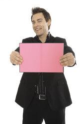 Man holding pink notebook, close-up - PKF00130