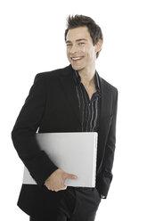 Young man holding laptop, close-up - PKF00127