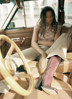 Colored woman sitting in car - PK00214