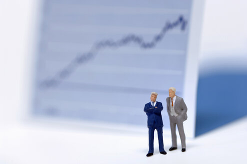 Figurines of businessmen in front of graph - ASF03367
