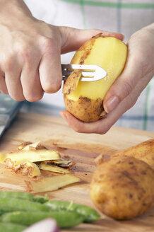 Man peeling potatoes, close-up - THF00607