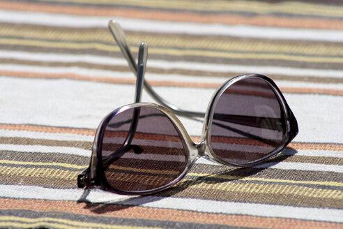 Sunglasses on striped cloth, close-up - TLF00175