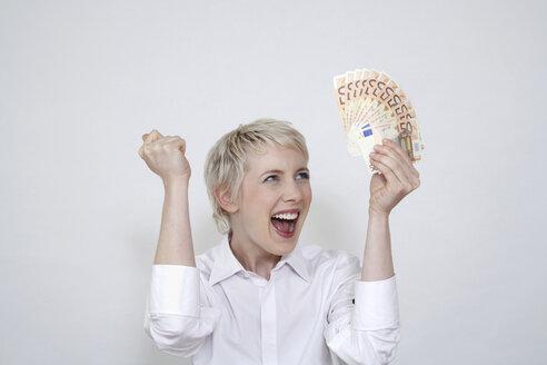 Young woman holding money, portrait - TCF00190