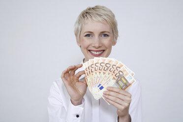 Young woman holding money, portrait - TCF00187