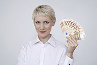 Young woman holding money, portrait - TCF00184