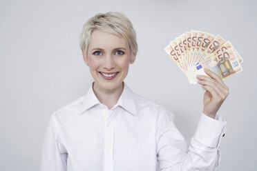 Young woman holding money, portrait - TCF00181