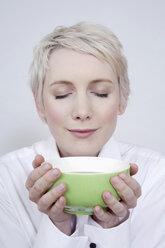 Young woman holding tea bowl, portrait - TCF00169