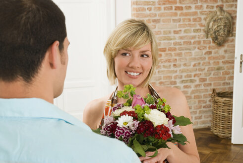 Man giving bunch of flowers to woman, close-up - NH00644