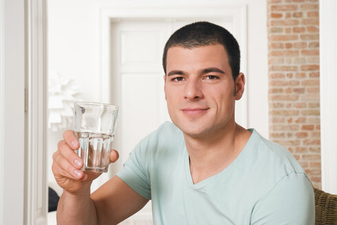 Man holding glass of water - NH00623