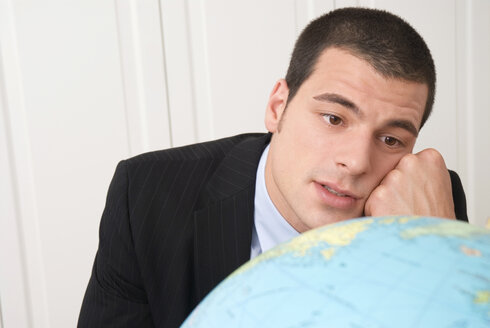 Businessman looking at globe, close-up, portrait - NH00599