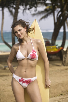 Guadeloupe, Caribbean, Young woman holding surfboard - AB00171