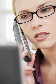 Woman in office using phone, close-up - VRF00047