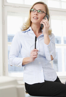 Woman in office using phone, close-up - VRF00036