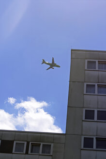 Aeroplane flying over house, low angle view - TL00261
