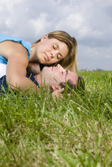 Couple lying in meadow, embracing - LDF00510