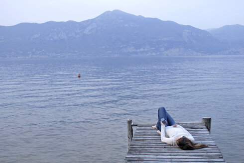 Italy, Lake Garda, Young woman (20-25) lying on jetty - DKF00126