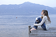 Italy, Lake Garda, Young woman (20-25) sitting on jetty holding personal stereo - DKF00123
