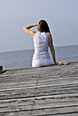 Italy, Lake Garda, Young woman (20-25) sitting on dock, rear view, close-up - DKF00117