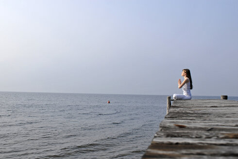 Italy, Lake Garda, Young woman (20-25) exercising yoga - DKF00114