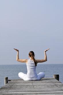 Italy, Lake Garda, Woman (20-25) exercising yoga on jetty - DKF00111
